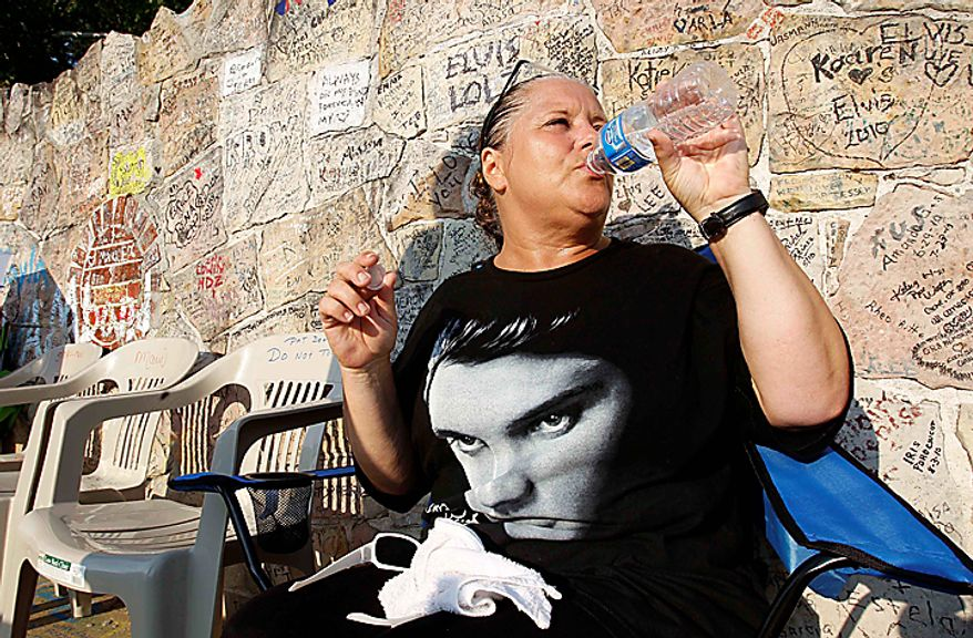 Elvis Presley fan Jeanine Hendershot, of Rocky Mount, N.C., drinks water as she waits in the heat outside Graceland mansion on Sunday, Aug. 15, 2010, in Memphis, Tenn. Presley fans from around the world are at Graceland for the annual nighttime procession past his grave on the eve of his death. Presley died at the home Aug. 16, 1977. (AP Photo/Mark Humphrey)
