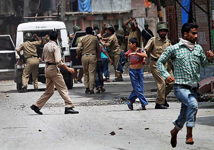 Indian security personnel beat Kashmiri Muslim protesters while detaining them during a protest in Srinagar, India, Monday, Aug. 16, 2010. Thousands of armed police and paramilitary soldiers patrolled nearly deserted streets in Srinagar and other major towns and enforced a strict curfew in most of the Kashmir region Monday. (AP Photo/Dar Yasin)