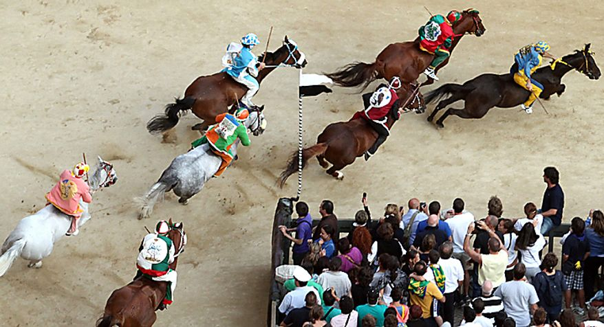 """Luigi Bruschelli """"Trecciolino"""" on  Istriceddu, at right, who represents the Tartuca neighborhood on his way to win the Palio, the famous break-neck bareback horse race around Piazza del Campo, Siena's main piazza, Italy, Monday, Aug. 16, 2010. The annual Palio pits Siena neighborhoods against one another and its a major tourist draw for this Tuscan city. Each neighborhood puts up a horse and rider to race three times around the slippery, dirt covered cobblestone track. (AP Photo/Paolo Lazzeroni)"""