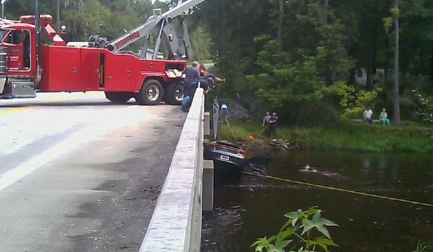 A car is lifted out of the North Edisto River in Orangeburg, S.C., on Monday. The bodies of two toddlers were recovered from the car and their mother was charged with suffocating them beforehand. (Associated Press)