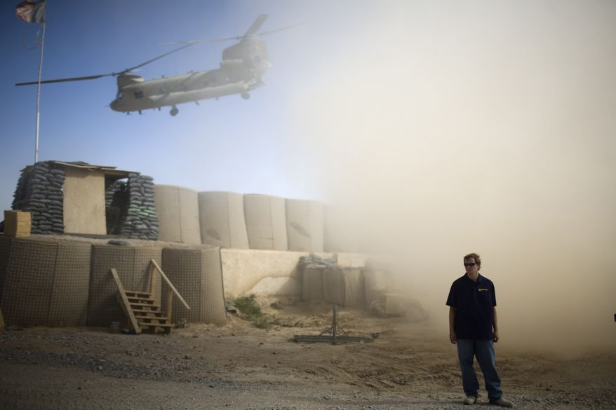 In this July 19, 2010, file photo, A U.S. contractor looks away from a dust cloud whipped up by a helicopter departing over the gatepost at Combat Outpost Terra Nova in Kandahar, Afghanistan. Afghan President Hamid Karzai on Tuesday, Aug. 17, 2010, set a four-month deadline for private security companies to cease operations in the country. (AP Photo/Rodrigo Abd, File)