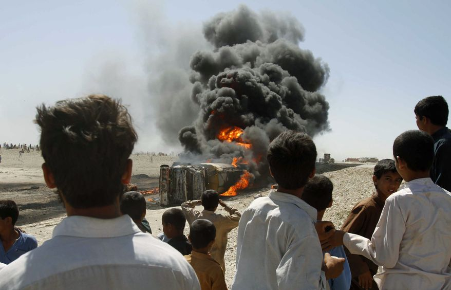 **FILE** In this photo from May 28, 2010, local Afghan residents watch a burning oil tanker that was carrying fuel supplies for NATO forces after it was allegedly attacked by Taliban on a Jalalabad highway, east of Kabul, Afghanistan. (Associated Press)