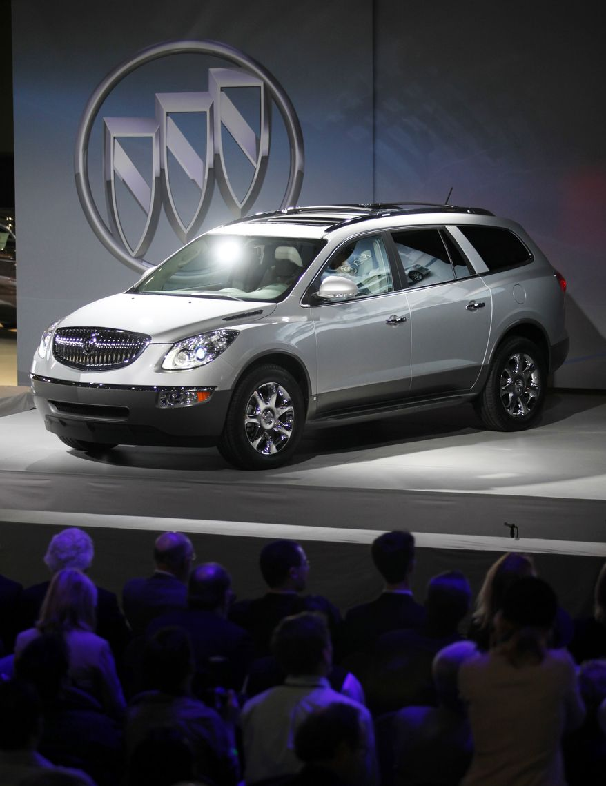 In thie file photograph taken Dec. 3, 2009, Buick introduces the new 2010 Buick Enclave at the Los Angeles Auto Show in Los Angeles. General Motors is recalling nearly 250,000 crossover vehicles worldwide to inspect second-row seat belts that could be damaged and not latch. (AP Photo/Damian Dovarganes, file)