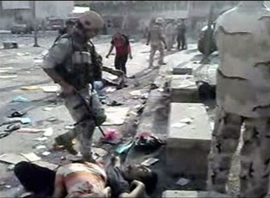 In this image from mobile phone video people look on the scene where at least 61 people were killed and 125 wounded in Iraq on Tuesday, Aug. 17, 2010, when a suicide bomber blew himself up among hundreds of army recruits who had gathered near a military headquarters in the capital, Baghdad. (AP Photo)