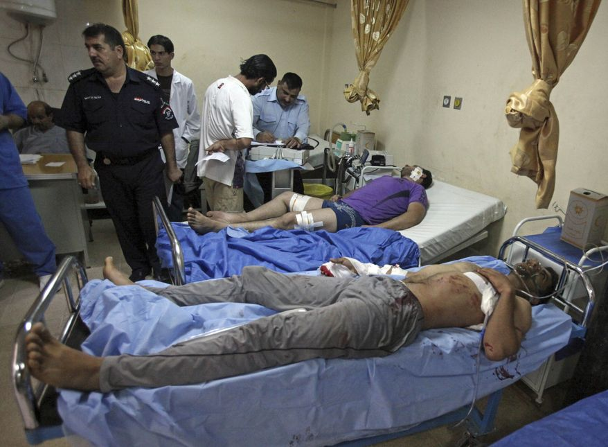Victims of a suicide attack are tended at a hospital in Baghdad, Iraq, Tuesday, Aug. 17, 2010. A suicide bomber blew himself up Tuesday among dozens of Iraqi army recruits who had gathered near a military headquarters in central Baghdad killing and wounding dozens of them. (AP Photo/Karim Kadim)