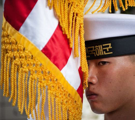 A South Korean sailor in the honor guard holds an U.S. flag as Secretary of State Hillary Rodham Clinton and Secretary of Defense Robert Gates lay a wreath at the Korean War Memorial, Wednesday, July 21, 2010, in Seoul, South Korea. (AP Photo/Paul J. Richards, Pool)
