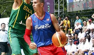 Puerto Rico's Carlos Arroyo, foreground, drives past Brazil's Anderson Varejao during the second period of the basketball game between Brazil and Puerto Rico,  Friday, Aug. 13, 2010 during the World Basketball Festival at Rucker Park in  New York. Puerto Rico defeated Brazil 77-55. (AP Photo/Mary Altaffer)