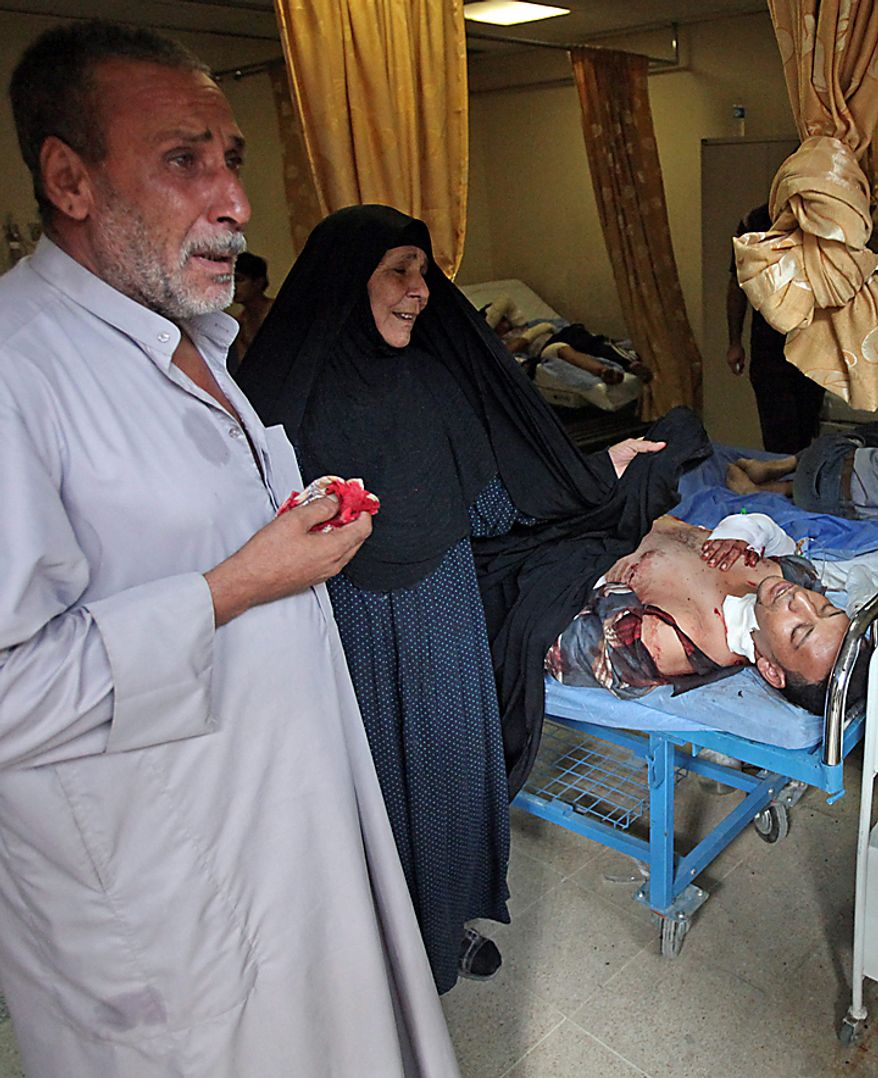 Parents of an injured man react as their son lies in a hospital bed in Baghdad, Iraq, Tuesday, Aug. 17, 2010. A suicide bomber blew himself up Tuesday among dozens of Iraqi army recruits who had gathered near a military headquarters in central Baghdad killing and wounding dozens of them. (AP Photo/Karim Kadim)