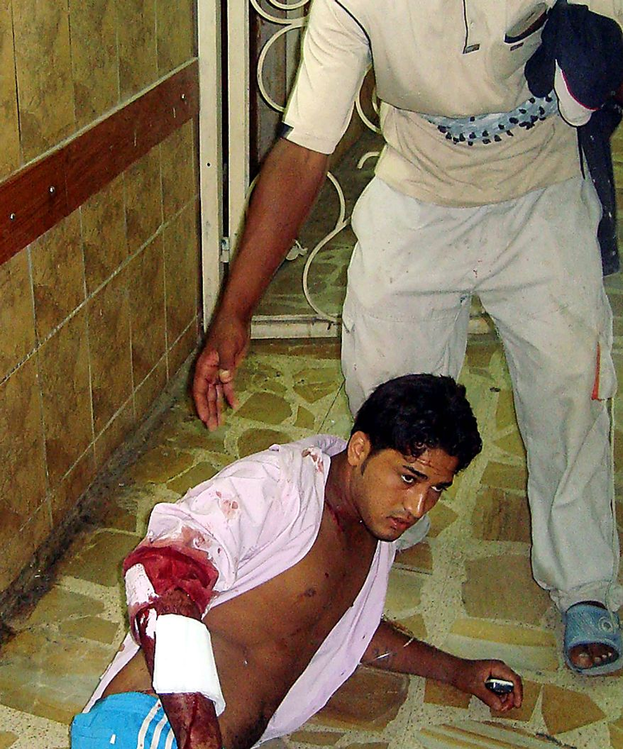 A victim of a suicide attack waits for a doctor on the floor of the emergency room of a hospital in Baghdad, Iraq, Tuesday, Aug. 17, 2010. A suicide bomber blew himself up Tuesday among hundreds of army recruits who had gathered near a military headquarters in central Baghdad killing and wounding dozens of them. (AP Photo)