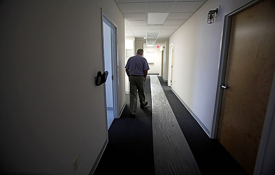 Dr. David Nichols walks down a  hallway of the new Tangier Island Health Clinic on Tangier Island, Va., Monday, Aug. 9, 2010.  The clinic is scheduled to open Aug. 29. Dr.  Nichols, who has been flying to Tangier to care for the residents for 30 years, has been diagnosed with terminal cancer. (AP Photo/Richmond Times-Dispatch, Bob Brown)