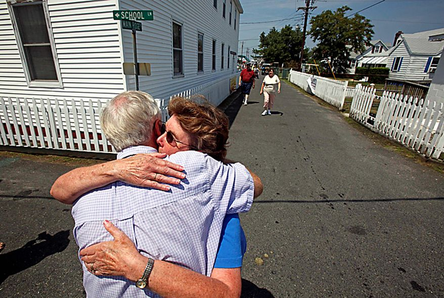 Dr. David Nichols gets a hug from Alice Pruitt near the new Tangier Island Health Clinic on Tangier Island, Va., Monday, Aug. 9, 2010.  The clinic is scheduled to open Aug. 29. Dr.  NIchols, who has been flying to Tangier to care for the residents for 30 years, has been diagnosed with terminal cancer. (AP Photo/Richmond Times-Dispatch, Bob Brown)