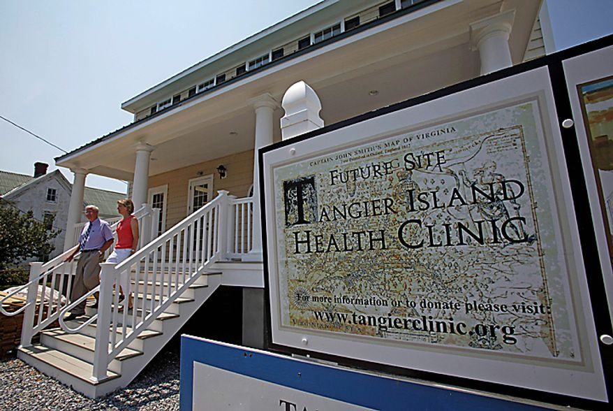 Dr. David Nichols, left, and Physician's Assistant Inez Pruitt walk out of the new Tangier Island Health Clinic on Tangier Island, Va., Monday, Aug. 9, 2010. The clinic is scheduled to open on Aug. 29. (AP Photo/Richmond Times-Dispatch,Bob Brown)
