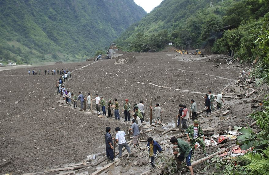People use logs and boards to pave a path into a village submerged by landslides in search for people buried in mud in Puladi township, in southwest China's Yunnan province, on Wednesday, Aug. 18, 2010. (AP Photo)