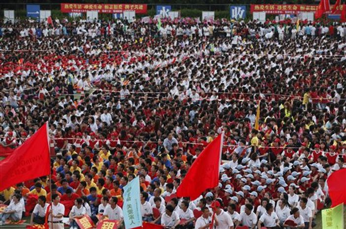 Foxconn workers shout slogans during a rally to raise morale at the heavily regimented factories inside the Foxconn plant in Shenzhen, south China, Guangdong province, Wednesday August 18, 2010. Following a string of suicides at its Chinese factories, Foxconn Technology Group raised workers' wages and installed safety nets on buildings to catch would-be jumpers. Now the often secretive manufacturer of the iPhone and other electronics is holding rallies for its workers to raise morale at the heavily regimented factories.  (AP Photo/Kin Cheung)