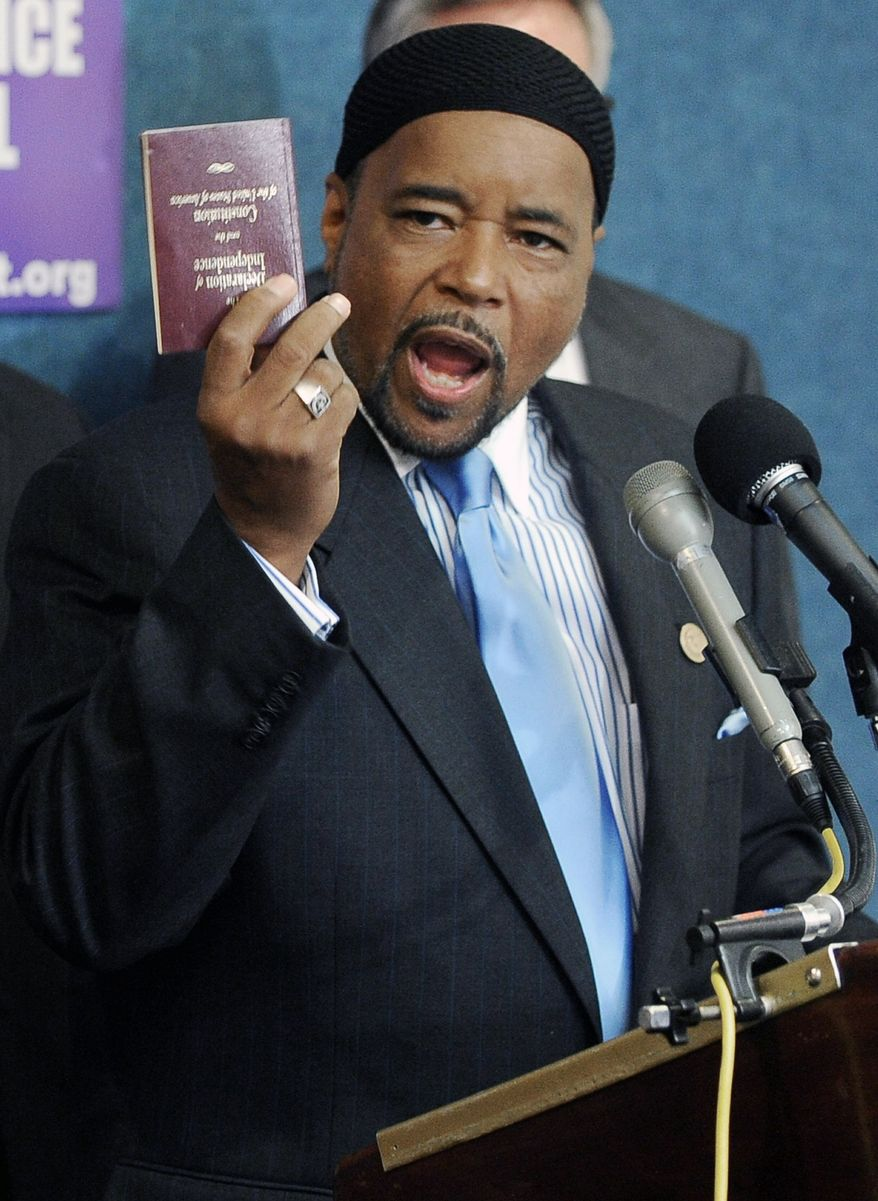 Imam Mahdi Bray, executive director of the Muslim American Society's Freedom Foundation, holds up a copy of the U.S. Constitution as he defends the mosque project in New York. (Associated Press)