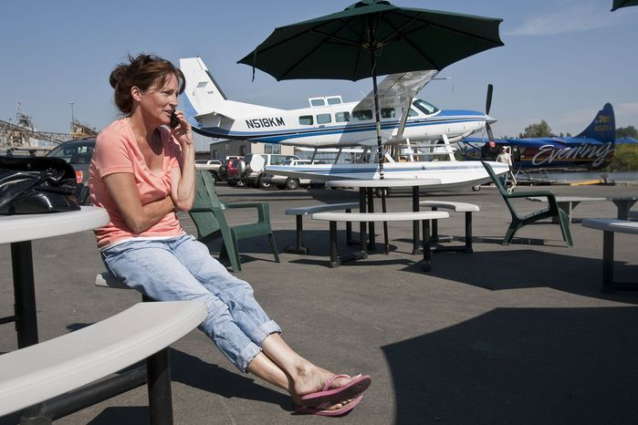Laura Joseph lets the people waiting for her know she may be late after the float plane she was aboard bound for Kenmore Air Harbor, Wash. from Lake Chelan, Wash. was intercepted by two U.S. fighter jets as it entered air space restricted due to the visit of President Obama on Tuesday, Aug. 17, 2010 in Kenmore, Wash. (AP Photo/The Seattle Times, Dean Rutz)