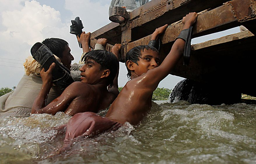 Young flood victims hang on the back of a truck as they cross a flooded area in Muzaffargarh, Punjab province,  Pakistan on Wednesday Aug. 18, 2010. Militants exploiting the flooding chaos in Pakistan clashed with police overnight, authorities said, as desperately needed international donations for the millions of victims picked up pace three weeks after the deluge began. (AP Photo/Aaron Favila)