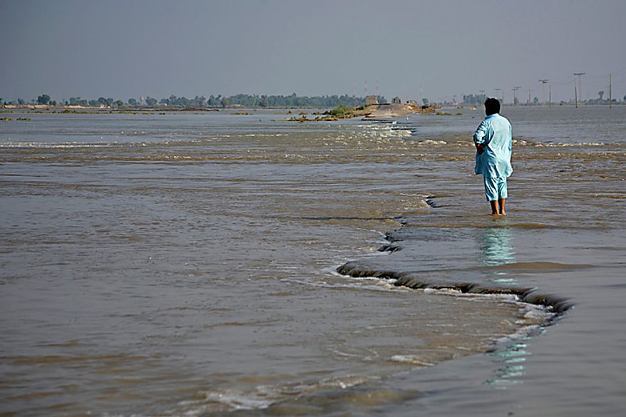 "A man watches a highway as it disappears under floodwaters in Sultan Kot, Pakistan, on Tuesday, Aug. 17, 2010. Prime Minister Syed Yousuf Raza Gilani said reconstruction and rehabilitation will be a ""big test"" for Pakistan once floodwaters recede. Photographer: Asad Zaidi/Bloomberg"