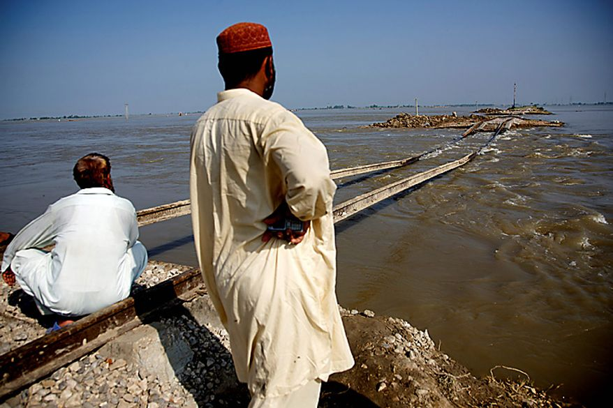 """People wait for an army boat near a railway track damaged by floodwaters in Sultan Kot, Pakistan, on Wednesday, Aug. 18, 2010. Prime Minister Syed Yousuf Raza Gilani said reconstruction and rehabilitation will be a """"big test"""" for Pakistan once floodwaters recede. Photographer: Asad Zaidi/Bloomberg"""
