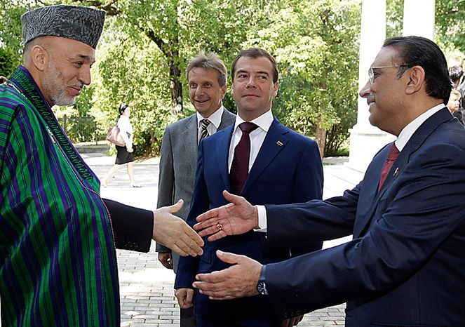 Afghan President Hamid Karzai, left, and Pakistani President Asif Ali Zardari shake hands as Russian President Dmitry Medvedev, center, looks on during their meeting  in the Bocharov Ruchei residence near Russia's Black Sea resort of Sochi, Wednesday, Aug. 18, 2010. Medvedev on Wednesday offered Pakistan support in dealing with catastrophic floods as he hosted leaders of Afghan, Pakistan and Tajikistan for talks on efforts to stabilize the region. (AP Photo/RIA-Novosti, Dmitry Astakhov, Presidential Press Service)