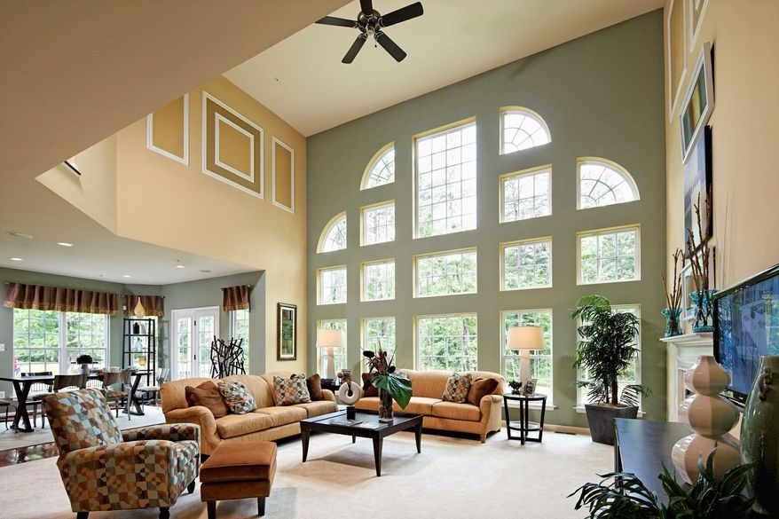 The Somerset model at the Villages of Savannah features a dramatic two-story family room with a wall of windows and an adjacent breakfast area and center-island kitchen wrapped in walls of windows.