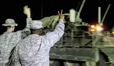 ASSOCIATED PRESS PHOTOGRAPHS U.S. Army Sgt. Jason Thompson (left) and Lt. Col. Nate Flegler wave to one of the last Stryker armored vehicles to leave Iraq.