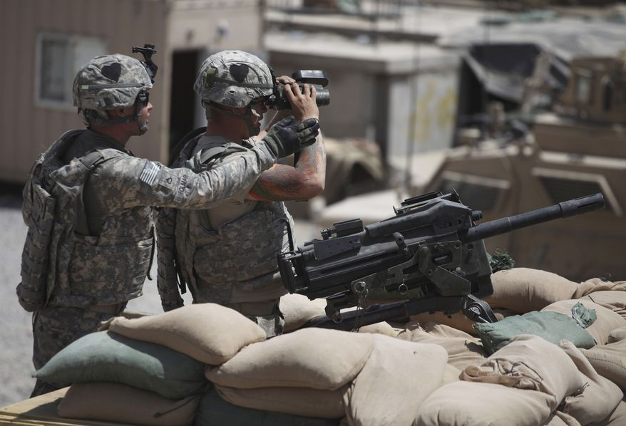 U.S. Army Pfc. Blake Folmar (left), with the 2nd Platoon, Delta Company of the 2nd Battalion, 502nd Infantry Regiment of the 101st Airborne Division, helps a fellow soldier who mans a Mark-19 automatic grenade launcher and uses binoculars to zero in on a nearby Taliban firing position from Forward Operating Base Howz-e-Madad in the Zhari district of Kandahar province in southern Afghanistan on Thursday, Aug. 19, 2010. (AP Photo/Brennan Linsley)