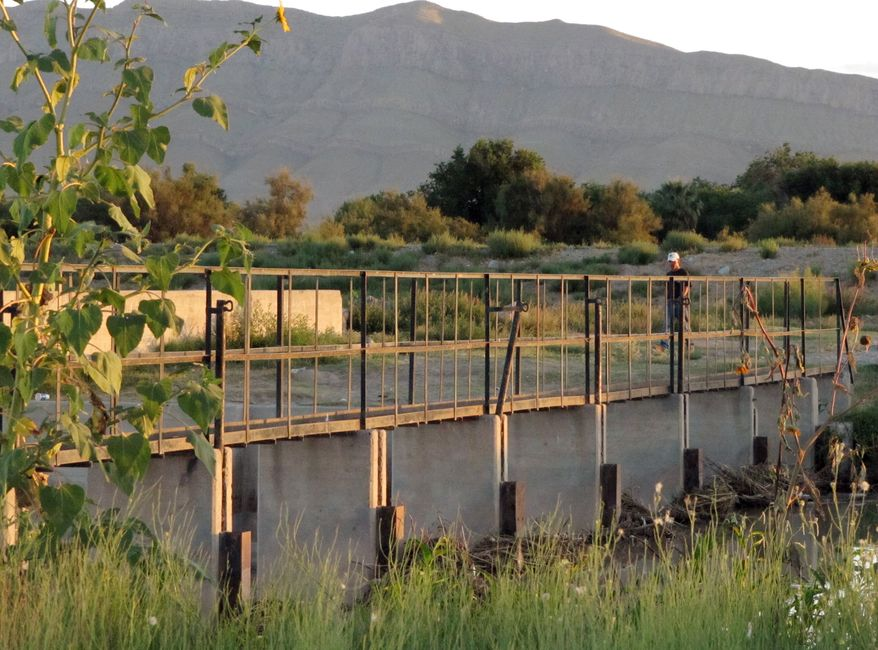 **FILE** An unidentified man in Mexico walks near a footbridge across the Rio Grande connecting the United States and Mexico near Acala, Texas, on Aug. 4, 2010. The bridge is one of two structures at opposite ends of a towering $2.4 billion west Texas stretch of steel border fence designed to block illegal entry. Though the International Boundary and Water Commission owns the bridges, which it calls grade control structures, both are unguarded paths into the United States from Mexico. (Associated Press)