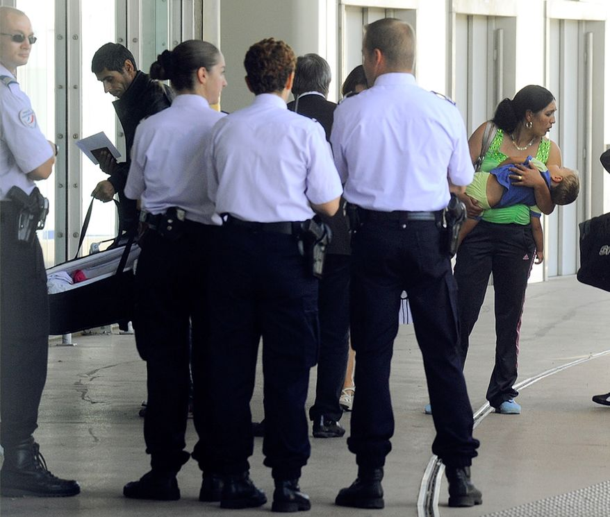Police guard a group of Gypsies, disembarking from a bus at the Lyon-Saint Exupery Airport in Lyon, France, en route to Bucharest, Romania, on Thursday, Aug. 19, 2010. A French Immigration Ministry official said 93 Roma are being repatriated to their native Romania as part of a crackdown by conservative President Nicolas Sarkozy. He has linked Gypsies, or Roma, to crime and spearheaded a campaign to dismantle their illegal camps and send some home to Eastern Europe. (AP Photo/Thomas Campagne)