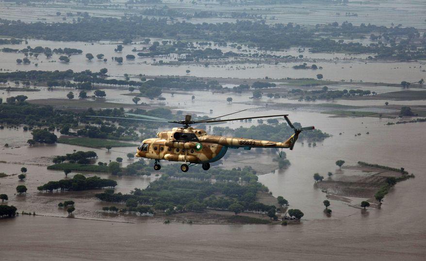 A helicopter with Sen. John Kerry and Pakistani President Asif Ali Zardari aboard flies over flooded areas of Jampur near Dera Ghazi Khan, Pakistan, on Thursday, Aug. 19, 2010. (AP Photo/B.K. Bangash)