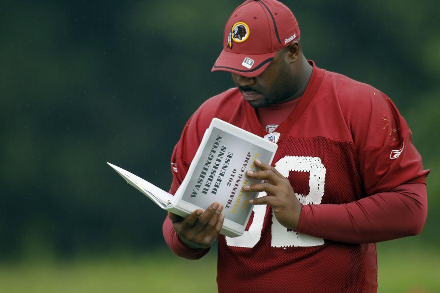ASSOCIATED PRESS Washington Redskins defensive lineman Albert Haynesworth checks the training camp play book during NFL football training camp at Redskins Park in Ashburn, Va. Wednesday, Aug. 18, 2010.