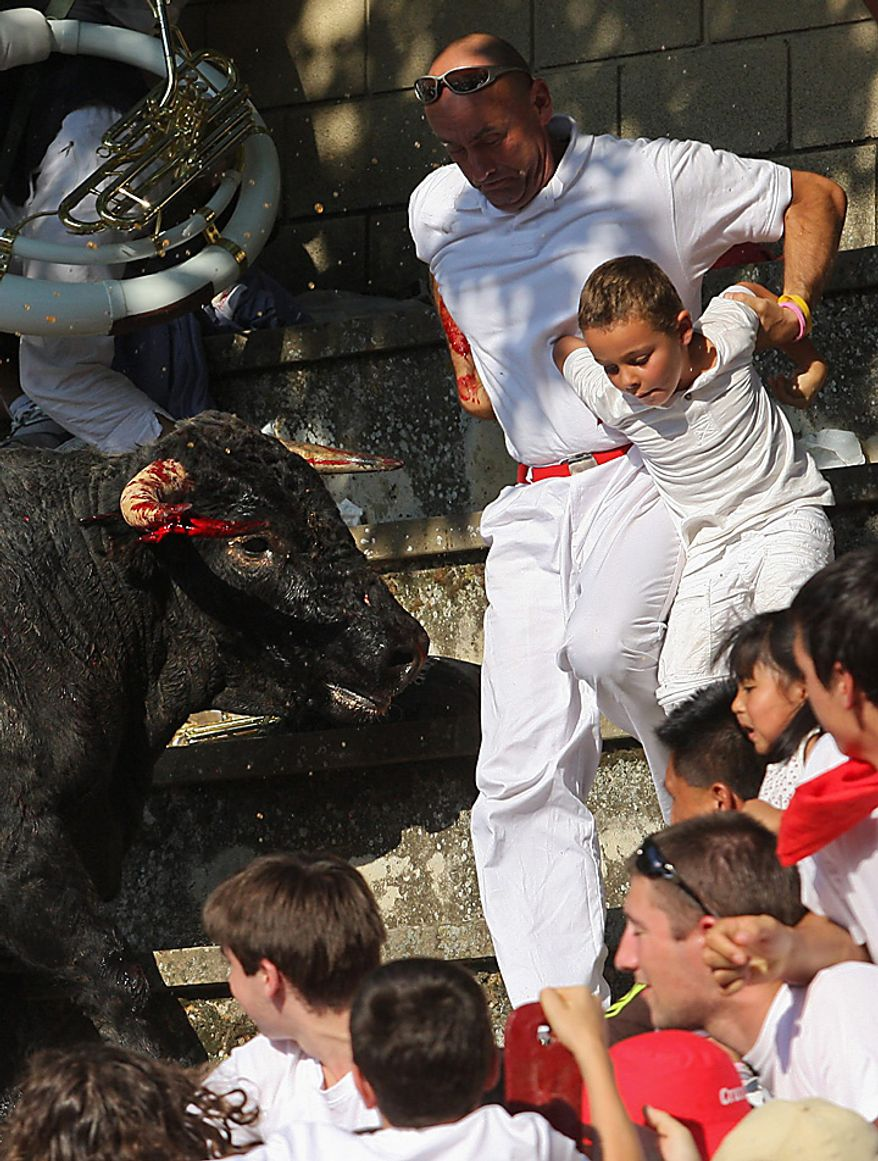 In this Wednesday, Aug. 18, 2010 picture made available Thursday, Aug 19. 2010 a bull charges against spectators after leaping into the stands during a bullfight in Tafalla, northern Spain. Up to forty people were injured when a bull leapt into the packed grandstands of a Spanish bullring and ran amok, charging and trampling on spectators. (AP Photo/Manuel Sagues)