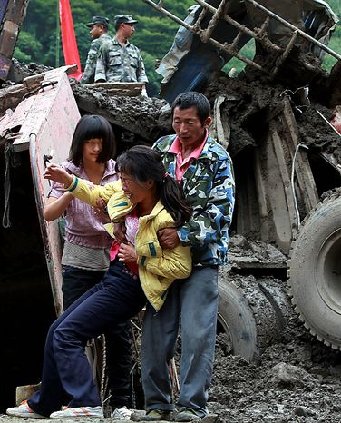 A woman grieves for relatives missing at the landslide hit Gongshan county in southwest China's Yunnan province, Thursday, Aug. 19, 2010. China struggled to cope with widespread storms that left dozens missing and presumed dead Thursday as rescuers cleaned up a mudslide-stricken town, while two passenger train cars plunged into a river after crossing a flood-damaged bridge. (AP Photo)