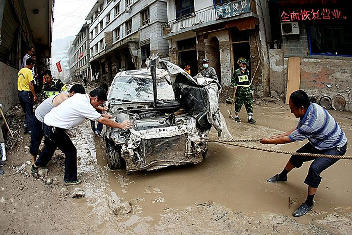 In this Wednesday, Aug. 18, 2010 photo, residents move a damaged car on a street covered by mud after mudslides in Zhouqu county, in northwest China's Gansu province. More rains are expected to hit all across China over in the coming days, with heavy rains forecast for Sichuan, Yunnan, Gansu, Shandong, Liaoning, Shaanxi, and Henan provinces, the Central Meteorological Station said. (AP Photo)