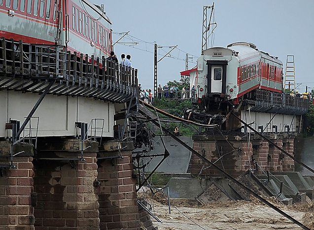 People look at a derailed passenger train on a collapsed bridge at the Shiting River in Guanghan in southwest China's Sichuan province, Thursday, Aug. 19, 2010. China struggled to cope with widespread storms that left dozens missing and presumed dead Thursday as rescuers cleaned up a mudslide-stricken town, while two passenger train cars plunged into a river after crossing a flood-damaged bridge. (AP Photo)