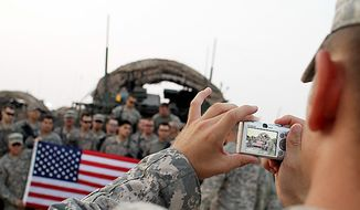 ** FILE ** In this Aug. 16, 2010, photo, U.S. Army soldiers from the 4th Battalion, 9th Infantry Regiment pose with an American flag for a photograph after crossing the border from Iraq into Kuwait. The soldiers are the last combat brigade to leave Iraq as part of the drawdown of U.S. forces. (AP Photo/Maya Alleruzzo)