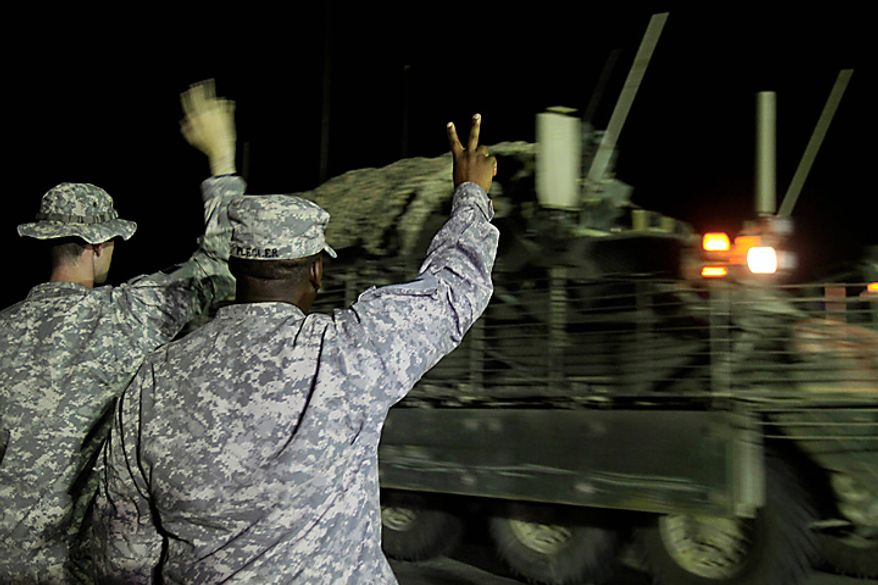 U.S. Army Sgt. Jason Thompson, left, and Lt. Col. Nate Flegler, right, wave to one of the last Stryker armored vehicles to leave Iraq as it crosses the border into Kuwait at the Khabari border crossing, Thursday, Aug. 19, 2010. The U.S. Army's 4th Brigade, 2nd Infantry Division is the last combat brigade to leave Iraq as part of the drawdown of U.S. forces.  (AP Photo/ Maya Alleruzzo)