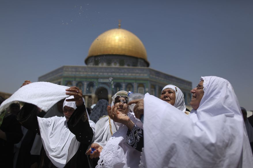 ** FILE ** In this Aug. 20, 2010, file photo, a Palestinian woman, right, splashes cold water on other female worshippers to cool them off as the temperature rises in front of the Dome of the Rock Mosque during the second Friday prayers of the Muslim holy month of Ramadan, in the Al-Aqsa Mosque compound in Jerusalem's Old City. (AP Photo/Muhammed Muheisen)