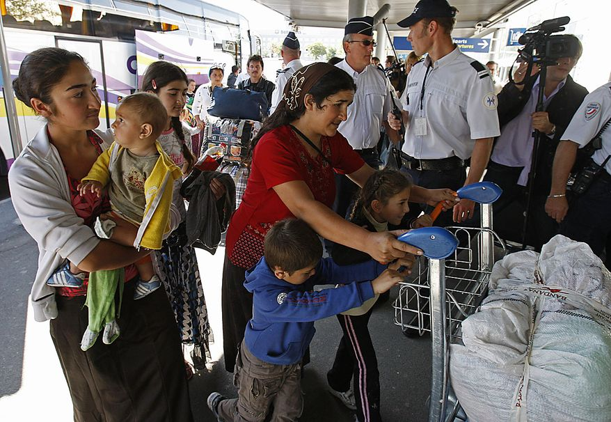Romanian gypsies are escorted by French police officers to the check-in desk at Roissy Charles de Gaulle airport, near Paris , Friday, Aug. 20, 2010.  France has expelled nearly 139 Gypsy or Roma, from Paris's airport to their native Romania as part of a very public effort by conservative President Nicolas Sarkozy to dismantle Roma camps and sweep them out of the country. (AP Photo/Michel Euler)