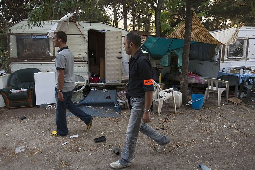 Two French plain clothes police officers walk through a  Gypsy squatters' camp in Aix-en- Provence, southern France, Thursday, Aug.19, 2010. France started to fly out Gypsies as part of a crackdown on illegal camps in the country.(AP Photo/Patrick Gherdoussi)