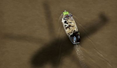 The shadow of a Pakistan Navy helicopter is seen as a residents ride in a boat carrying rescued farm animals during an emergency aid distribution, near Bachel in  Sindh Province, southern Pakistan, Thursday, Aug. 19, 2010. (AP Photo/Kevin Frayer)