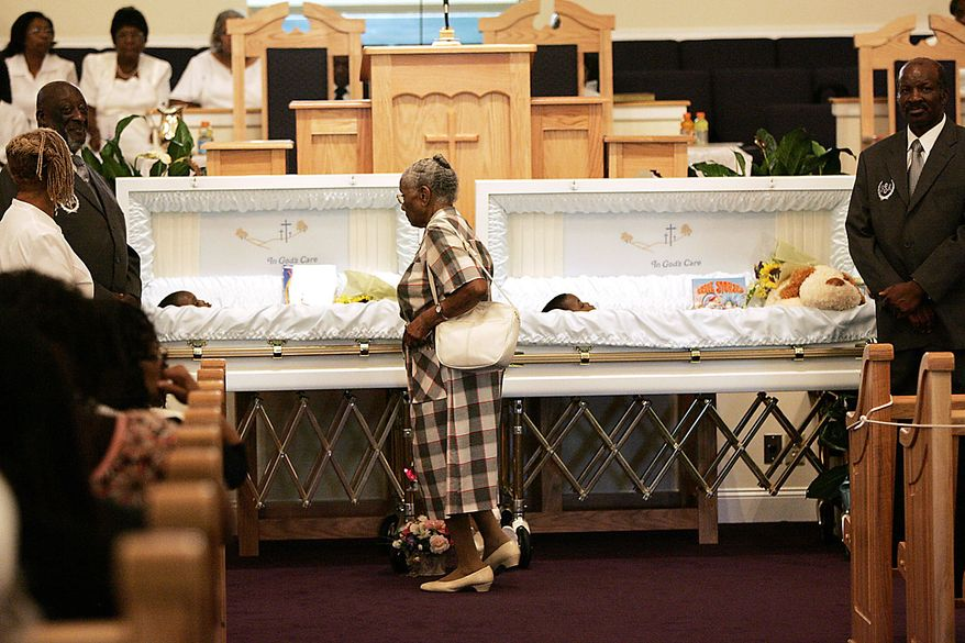 An unidentified mourner walks past the open caskets of Devean Duley and Ja'van Duley before their funeral service Friday, Aug. 20, 2010, at St. Paul Baptist Church in Orangeburg, S.C. The boys' 29-year-old mother, Shaquan Duley, was not allowed to attend. Investigators say she confessed to smothering her children Sunday night then staging a car accident to cover up the deaths.  (AP Photo/Mary Ann Chastain)