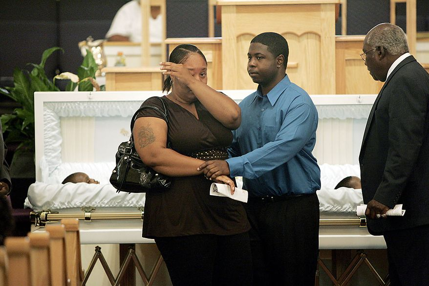 A couple who would only identify themselves as family wipe away tears after viewing the caskets of Devean Duley, 2, and Ja'van Duley, 18 months, at their funeral Friday, Aug. 20, 2010, at St. Paul Baptist Church in Orangeburg, S.C. The boys' 29-year-old mother, Shaquan Duley, was not allowed to attend. Investigators say she confessed to smothering her children Sunday night then staging a car accident to cover up the deaths. (AP Photo/Mary Ann Chastain)