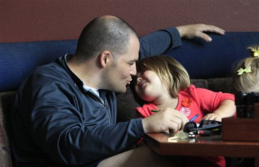 U.S. Army Capt. Mark Fisher, left, leans down to kiss his daughter Madeline, 2, as he sits to have lunch with her and another daughter after arriving at nearby Joint Base Lewis-McChord the evening before Thursday, Aug. 19, 2010, in DuPont, Wash. Fisher had just returned from a nearly one-year tour in Iraq, his second there. Seven years and five months after the U.S.-led invasion, the last American combat brigade was leaving Iraq, well ahead of President Barack Obama's Aug. 31 deadline for ending U.S. combat operations there. (AP Photo/Elaine Thompson)