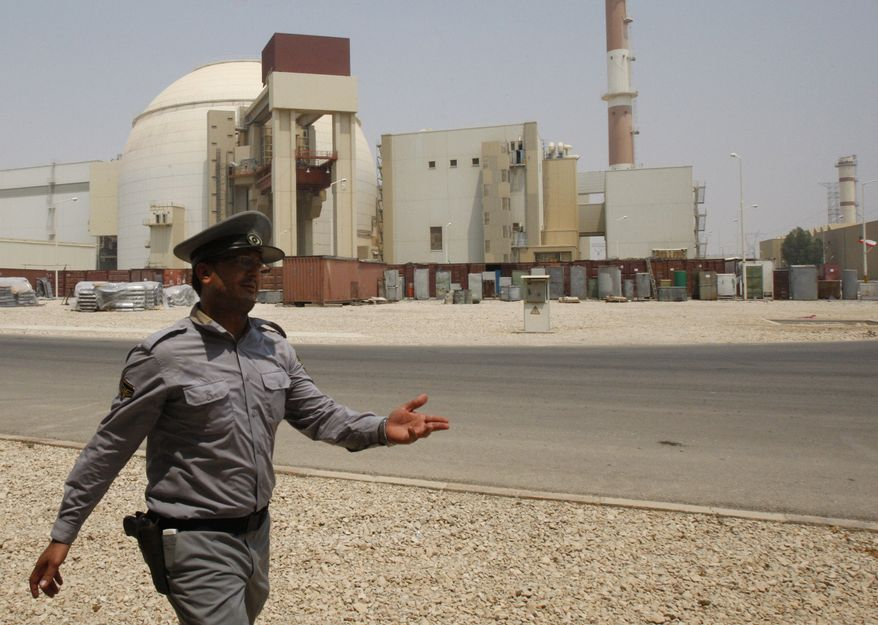 An Iranian security directs media at the Bushehr nuclear power plant, with the reactor building seen in the background, just outside the southern city of Bushehr, Iran, on Saturday, Aug. 21, 2010. Iranian and Russian engineers began loading fuel Saturday into Iran's first nuclear power plant, which Moscow has promised to safeguard to prevent material at the site from being used in any potential weapons production. (AP Photo/Vahid Salemi)