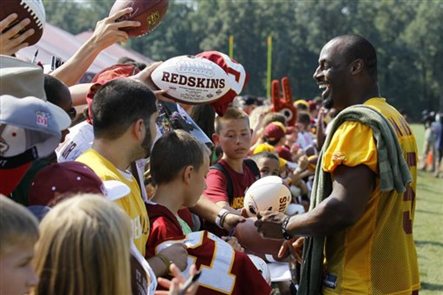 Washington Redskins quarterback Donovan McNabb smiles as he signs autographs for fans after the last day of their NFL football training camp at Redskins Park in Ashburn, Va.,  Thursday, Aug. 19, 2010.(AP Photo/Alex Brandon)