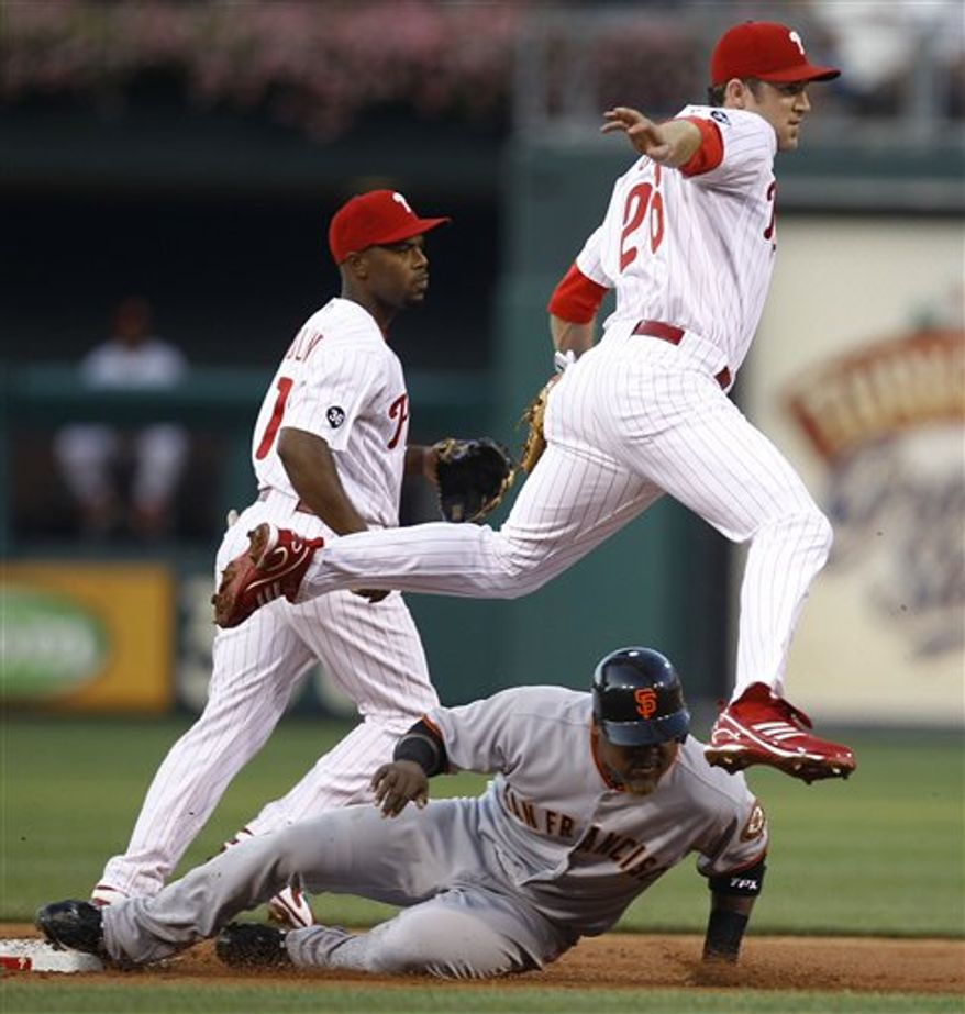 Philadelphia Phillies second baseman Chase Utley leaps over San Francisco Giants' Juan Uribe after making the throw to first for a double play as Phillies shortstop Jimmy Rollins looks on in the first inning of a baseball game in Philadelphia, Thursday, Aug. 19, 2010. (AP Photo/Matt Rourke)