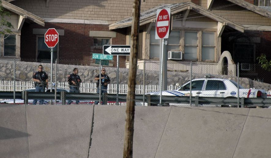 ** FILE ** El Paso police officers lookout into the Mexican border city of Ciudad Juarez after a heavy gun battle erupted in Ciudad Juarez, Mexico, Saturday, Aug. 21, 2010. (AP Photo/Raymundo Ruiz)