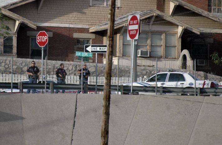 ** FILE ** El Paso police officers lookout into the Mexican border city of Ciudad Juarez after a heavy gun battle erupted in Ciudad Juarez, Mexico, Saturday, Aug. 21, 2010. (AP Photo/Raymundo Ruiz)