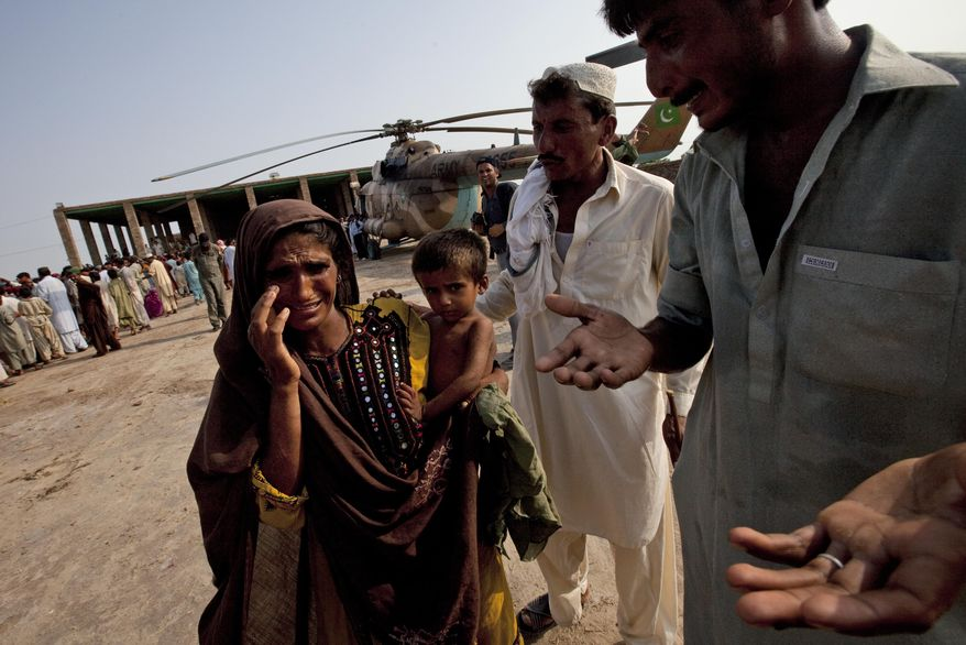 A Pakistani woman weeps as she stands with others crowding around a Pakistan Army helicopter after it arrived to deliver food aid for the United Nations World Food Program in the flood encircled village of Tul in Sindh Province, southern Pakistan, Friday, Aug. 20, 2010. (AP Photo/Kevin Frayer)